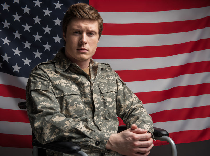 Waist up portrait of serious disabled military man looking at camera with hard look. He is sitting in wheelchair with his hands folded in the lock. USA flag on background