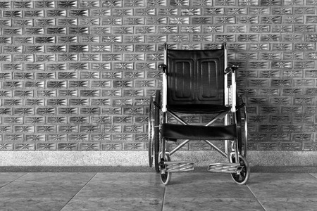 42762180 - black and white wheelchair rolls on the sidewalk.